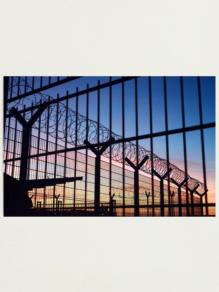 Alternate view of View through a barbed wire fence with beautiful colourful sunset sky in Dieppe France Photographic Print