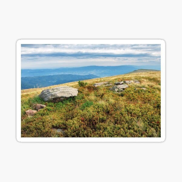 grassy meadow with boulder on top of a hill Sticker
