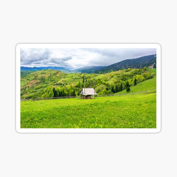 hay shed on a grassy field in mountains Sticker
