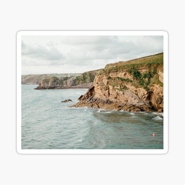 Powerful Ocean Waving Near Rocky Cliffs Under Cloudy Sky Sticker