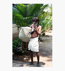 A worker carries a bg of laundry in Cochin India Photographic Print