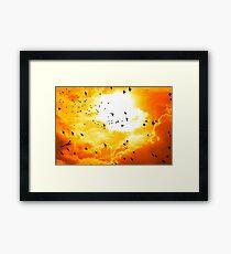 birds flying into a bright orange sunset Framed Print
