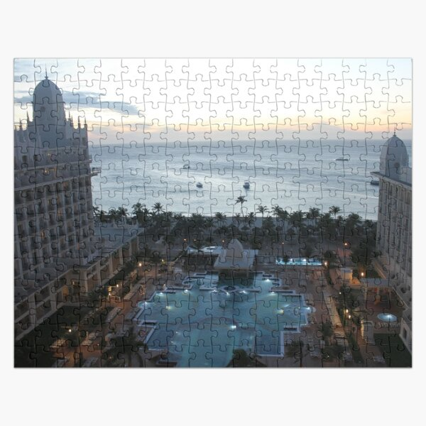 Riu Palace Aruba, evening time, pink clouds, empty water pool, palm trees on the beach, darkness and nigh light Jigsaw Puzzle