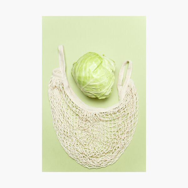 Trendy string bag with fresh young cabbage over light green background. Zero waste sustainable lifestyle concept. Photographic Print