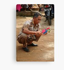 old man holding toy Canvas Print