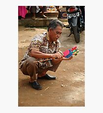 old man holding toy Photographic Print