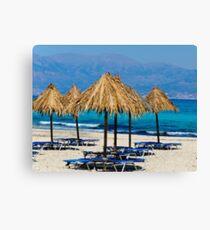Sunbeds and umbrellas on the beach Canvas Print