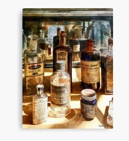 Medicine Bottles in Glass Case Canvas Print