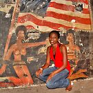 African Girl in front of a Graffiti of Black gils and US Flag by Remo Kurka