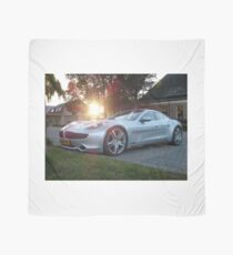 2012 Fisker Karma electric supercar against a sunset Scarf