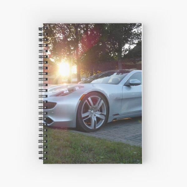 2012 Fisker Karma electric supercar against a sunset Spiral Notebook