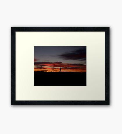 Fisherman ponders the morning sun Framed Print