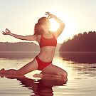 Woman practicing yoga on the water doing Pigeon pose in morning sunlight art photo print by ArtNudePhotos