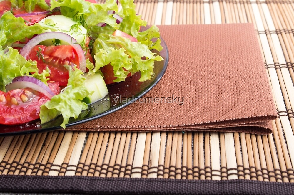 Closeup view of a plate with fresh salad of raw tomatoes by vladromensky