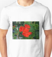 Red powerful color flower and green leaves background. Unisex T-Shirt