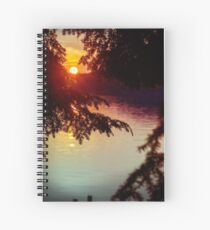 setting sun shining through the trees and reflecting off a northern lake Spiral Notebook