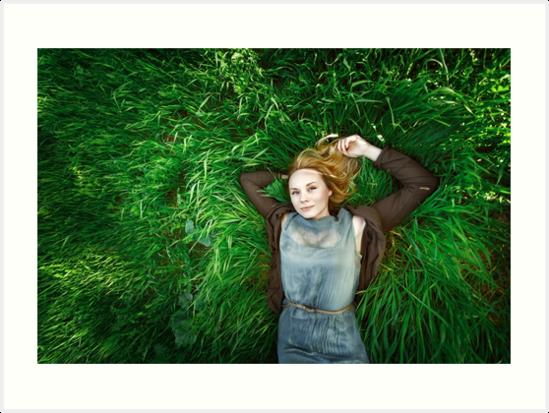 Beautiful meditative young woman lying in the grass by dariazu