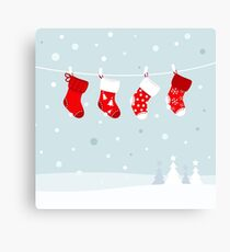 Cute christmas stockings, winter snow in background Canvas Print
