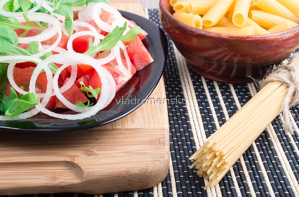 Black plate with fresh salad of tomatoes, onions and arugula by vladromensky