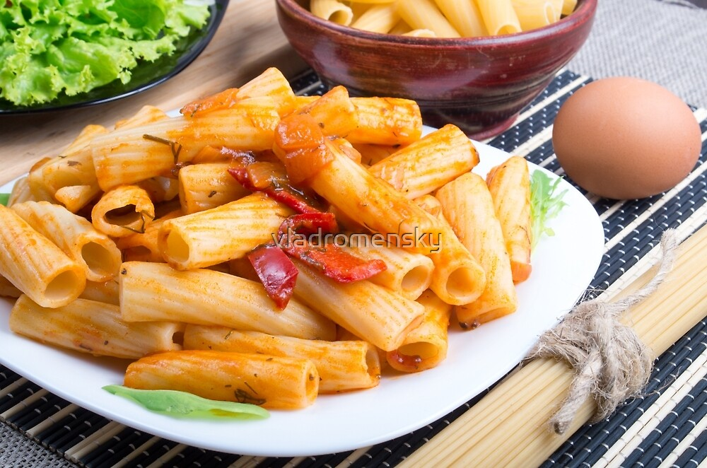 View closeup on a dish of rigatoni pasta with vegetable sauce by vladromensky