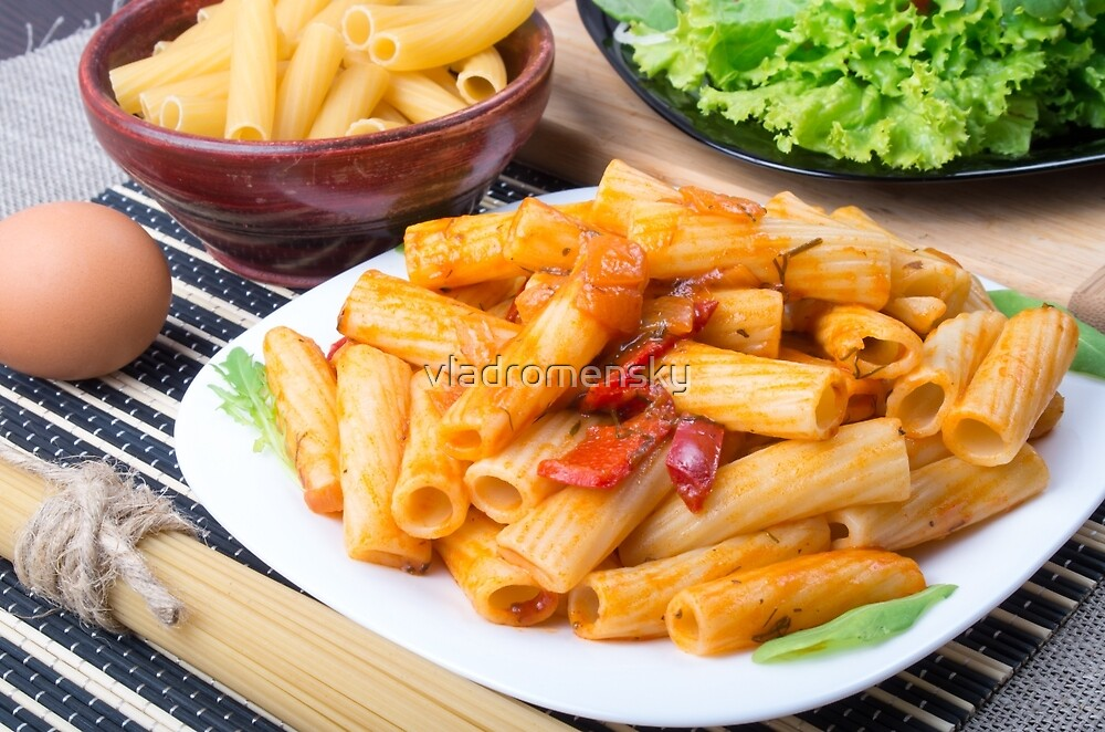 Cooked rigatoni pasta, seasoned with pepper and arugula by vladromensky