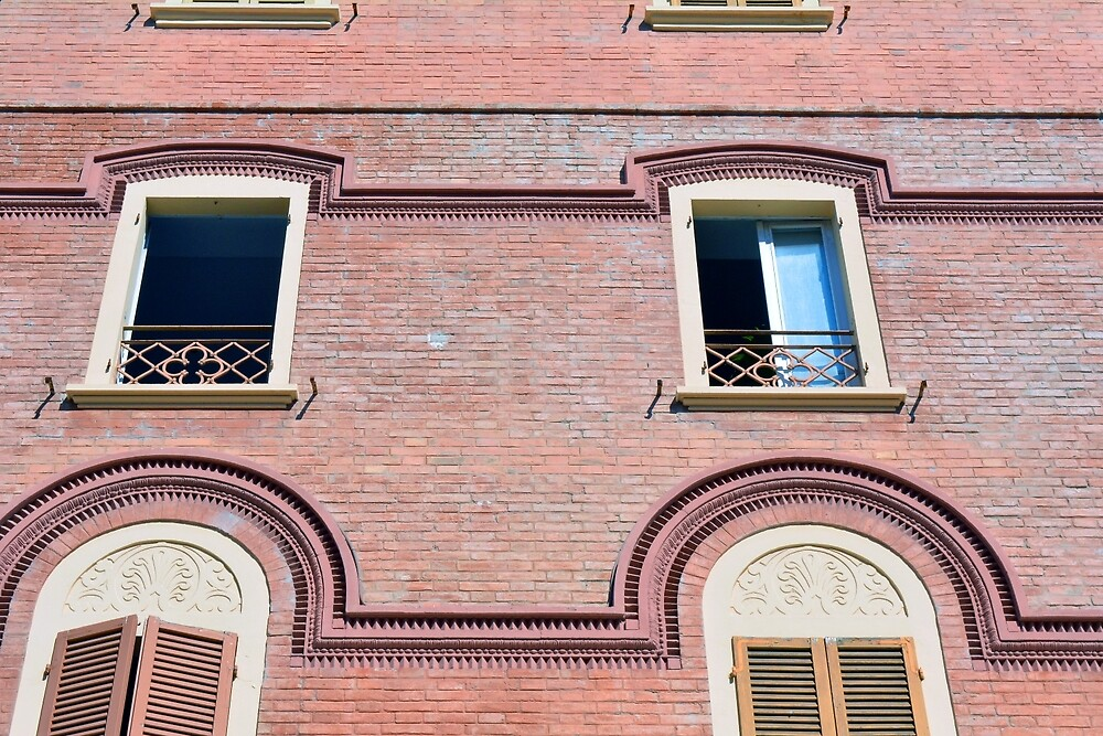 Facade detail with decorative windows and red brick  by oanaunciuleanu