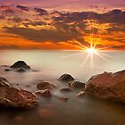 Red Sunset on foggy rocks by Delfino