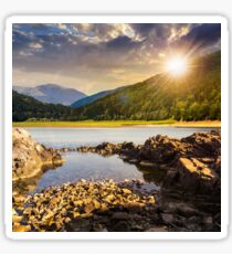 lake shore with stones near pine forest on mountain at sunset Sticker