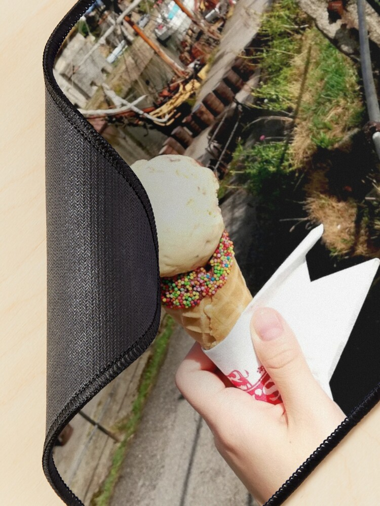 Alternate view of Person holding an ice cream cone near a sailboat and an old building, sunny day with clouds in the sky Mouse Pad
