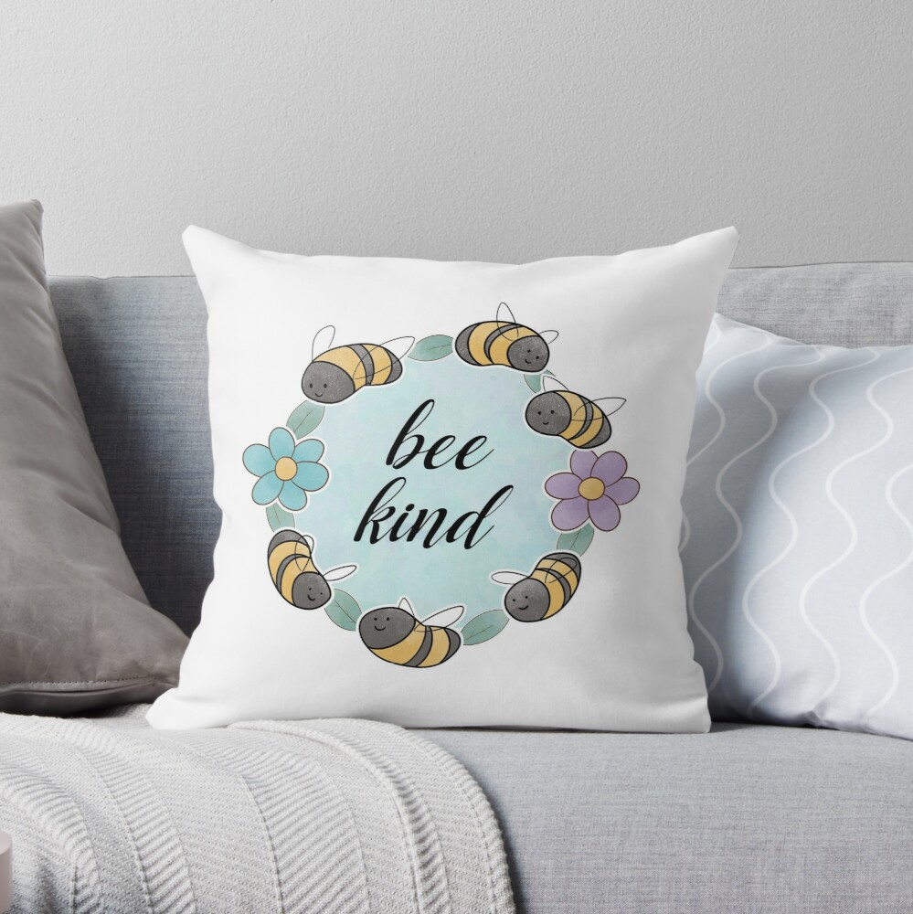 bee kind throw pillow with a circle framed with bees, leaves, and flowers