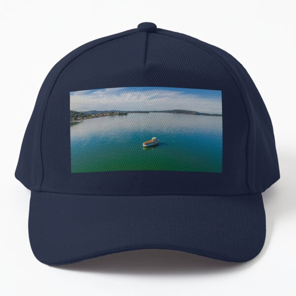 Daytime aerial waterscape with older boat Baseball Cap