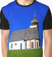 Beautiful little church in Alps. Sunny day, green grass on the hill and blue sky. Austria. Graphic T-Shirt