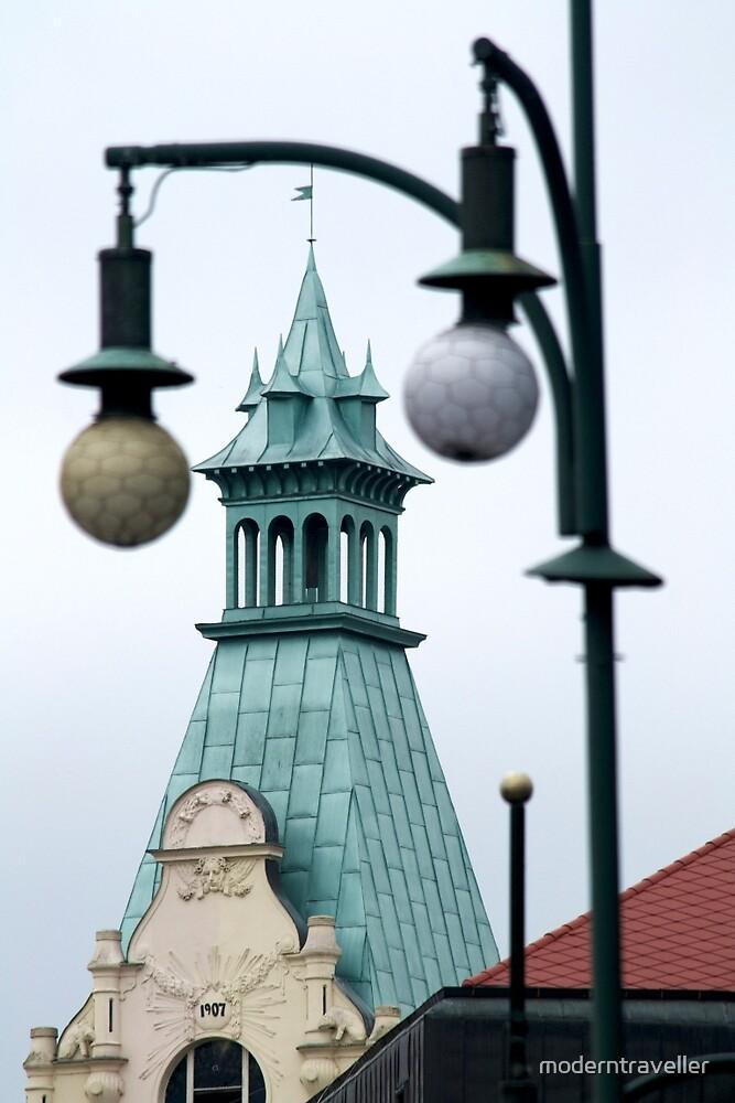 Prague spire through lights by moderntraveller