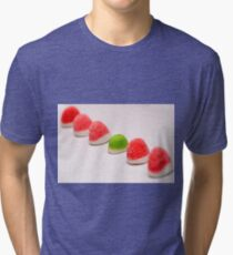 A line of red colourful sugared jelly sweets with one green one in the centre Tri-blend T-Shirt