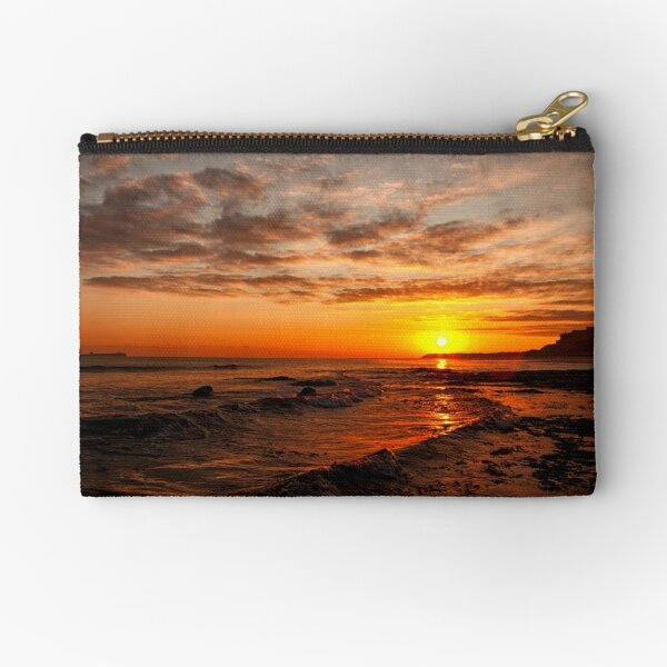 Sunrise across the waves to Bamburgh Castle, Northumberland, UK Zipper Pouch