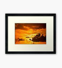 flocks of starlings flying into an orange sunset sky Framed Print