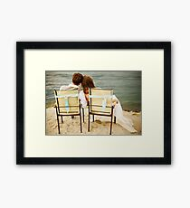Newlyweds couple sitting near water on the beach Framed Print