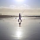 lone fisherman fishing on the sunny Kerry beach by morrbyte
