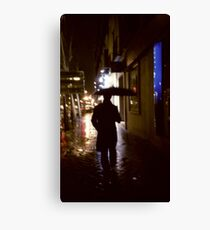 Man walking in street at night in rain color 35mm analogue photojournalism portrait photograph Canvas Print