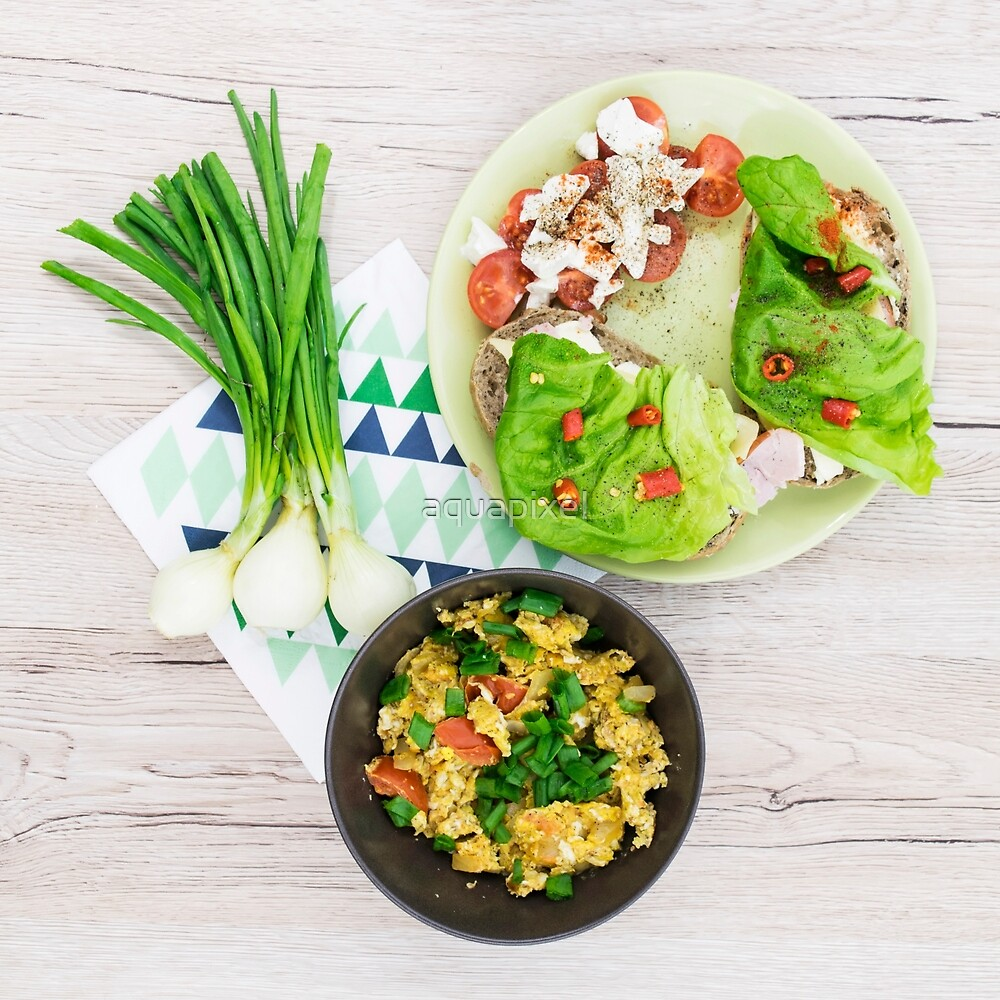 Scrambled eggs in the brown bowl. Sandwiches with lettuce and hot peppers. Wooden background. Top view by aquapixel