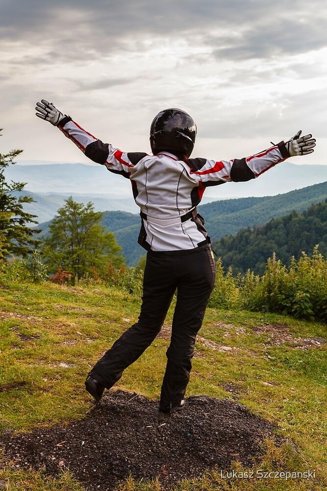 Happy biker with her hands up against mountain view by Lukasz Szczepanski