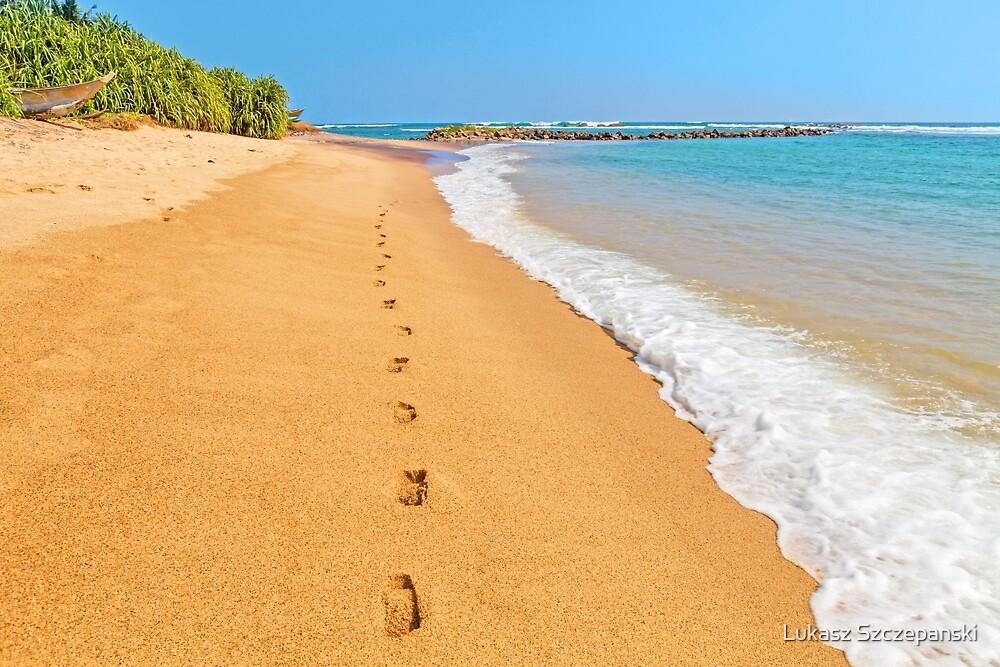 Footprints on sunny beach by emerald sea by Lukasz Szczepanski
