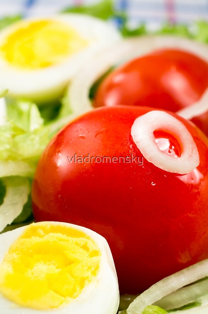 Cherry tomatoes and boiled eggs in a salad with lettuce leaves by vladromensky