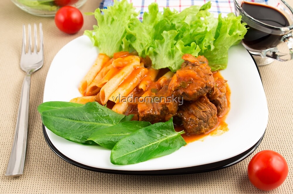 Dish of beef goulash with penne pasta, lettuce and spinach by vladromensky