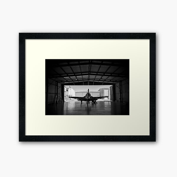 Silhouette of a P-51 Mustang fighter aircraft in a hangar Framed Art Print