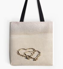 Two hearts drawn in the sand on a beautiful beach Tote Bag