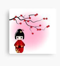 Japanese kokeshi doll at sakura blossoms Canvas Print