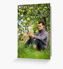 Teenager reading a book in the orchard Greeting Card