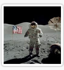 Apollo 17 astronaut stands near the American flag on the lunar surface. Sticker