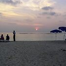 Host gesturing to a tourist family at sunrise in the Lakshadweep Islands by ashishagarwal74